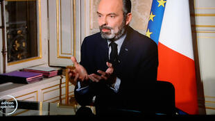 French Prime Minister Édouard Philippe is seen on a TV screen as he speaks from his office during the evening news broadcast of French public television channel France 2 on March 17, 2020 in Paris on the day a strict lockdown came into effect in France to stop the spread of the novel coronavirus.