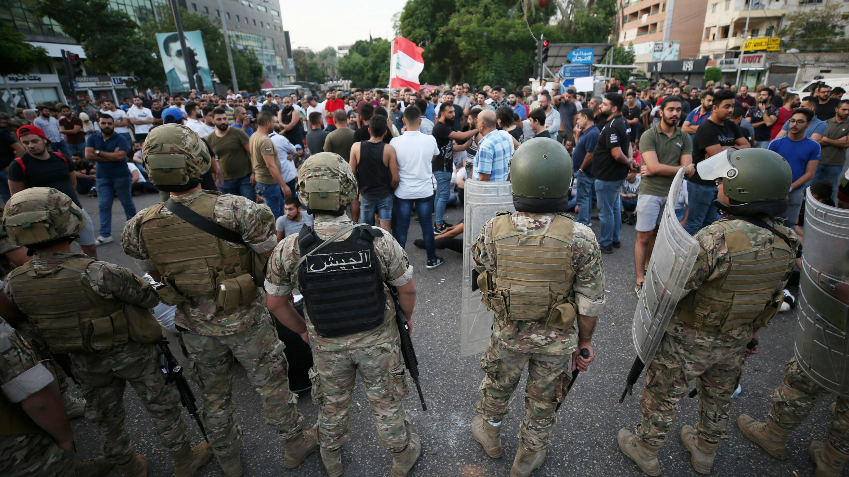Soldados del ejército libanés hacen guardia mientras los manifestantes participan en una protesta contra el gobierno por una crisis económica en la ciudad portuaria de Sidón, Líbano, el 18 de octubre de 2019.