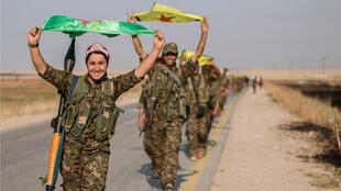 Combatientes kurdos con banderas de su partido en Tel Abyad, gobernación de Raqa, Siria, luego de la toma de control de la zona, el 15 de junio de 2015.