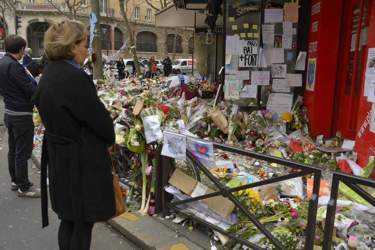 Gente reunida el 27 de noviembre de 2015 frente al café La Belle Equipe en el distrito 11 de París, para llorar a las víctimas durante un homenaje nacional a las 130 personas muertas en los ataques del 13 de noviembre de 2015 en París, Francia.
