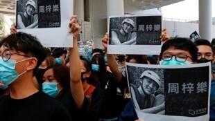 Des manifestants brandissant vendredi des photos de l'étudiant de 22 ans décédé après un affrontement avec la police.