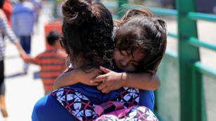 Una migrante centroamericana carga a su hija justo después de que fuera enviada a México de vuelta, desde EE. UU., según los Protocolos de Protección al Migrante (MPP), en Tijuana, México, el 18 de julio de 2019.