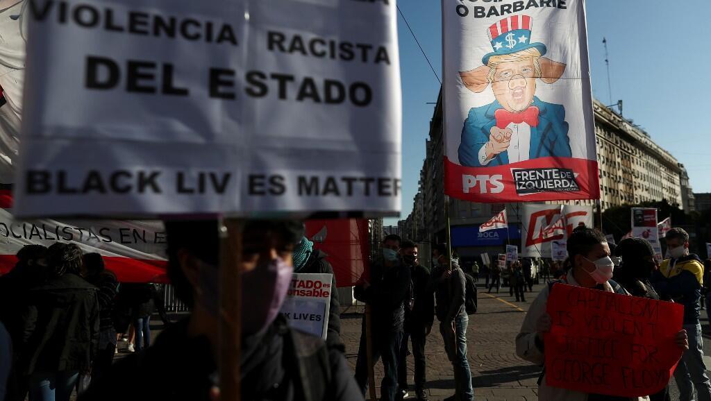Manifestantes sostienen una bandera que representa el rostro del presidente estadounidense Donald Trump, durante una protesta contra la violencia policial. En Buenos Aires, Argentina, el 2 de junio de 2020.