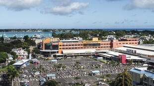 An aerial shot taken in April 2020 shows people waiting while adhering to social distancing in a parking lot before entering a supermarket in Grand Baie, Mauritius; the country has declared wary victory over the coronavirus