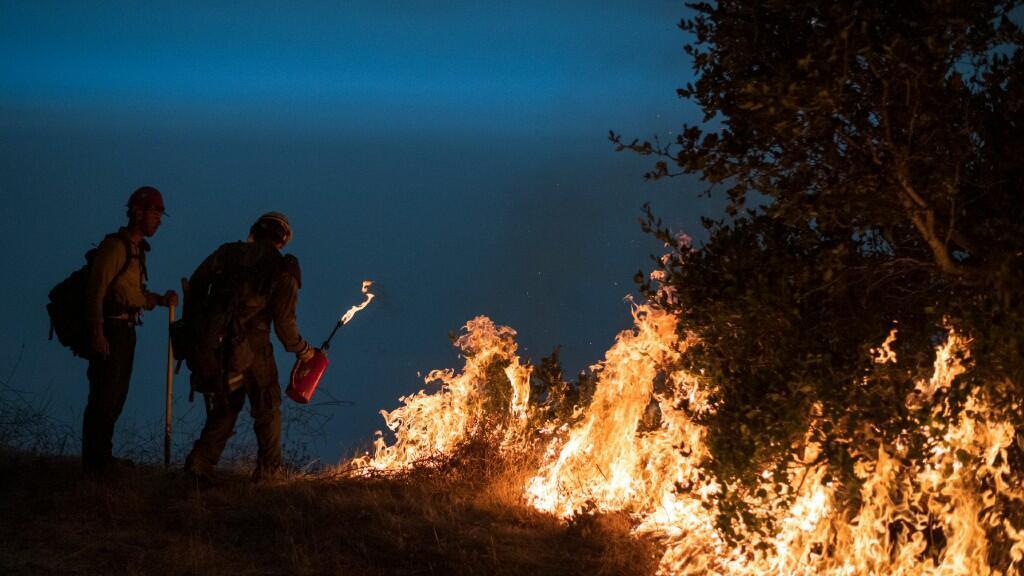 Dos bomberos crean un incendio controlado para detener el avance de las llamas de otro que les amenaza. En Big Sur, California, el 11 de septiembre de 2020.
