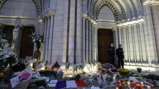أكاليل ورد وشموع والعلم الفرنسي أمام كاتدرائية نوتردام في نيس حدادا على أرواح ضحايا الاعتداء. 29/10/2020
