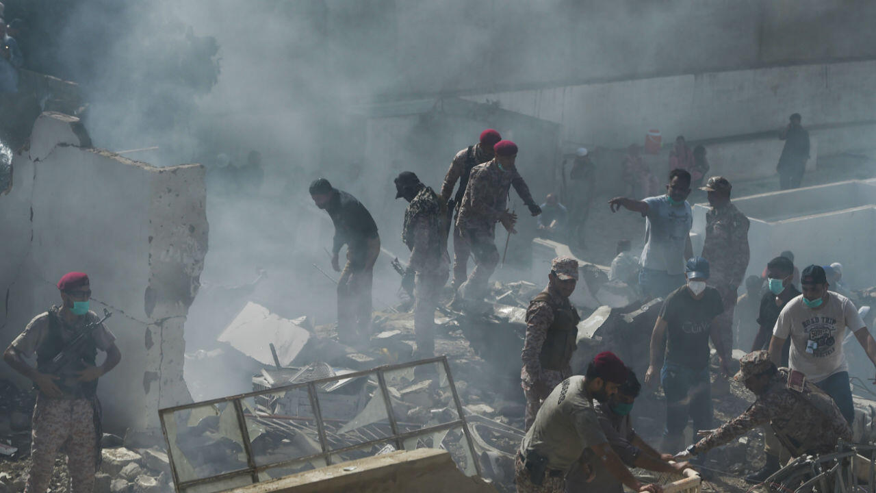 The security services and the army search the site of a plane crash in Karachi on May 22, 2020.