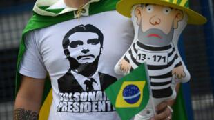 Un supporter du candidat d'extrême droite Jair Bolsonaro brandit une poupée gonflable représentant l'ex-président Lula en tenue de prisonnier.