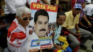 Una mujer sostiene una foto del presidente de Venezuela, Nicolás Maduro, durante una concentración oficial frente al Palacio Miraflores, Caracas, Venezuela. 4 de abril, 2018.