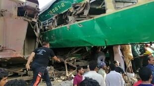 Rescuers and onlookers gather around the twisted wreckage of train carriages after the accident