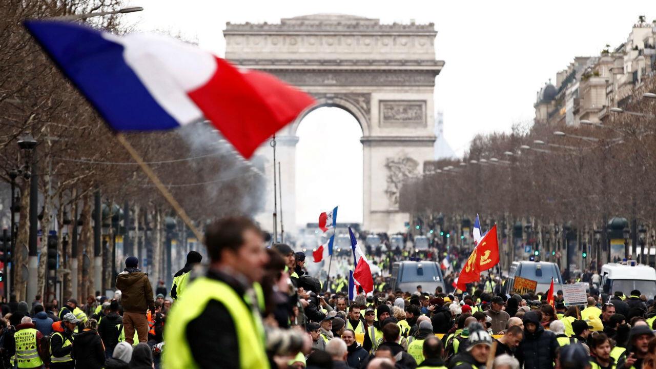"""Un manifestante que usa un chaleco amarillo agita una bandera francesa mientras se para en los Campos Elíseos, cerca del Arco de Triunfo, durante una manifestación del movimiento """"chalecos amarillos"""" en París, Francia, el 2 de marzo de 2019."""