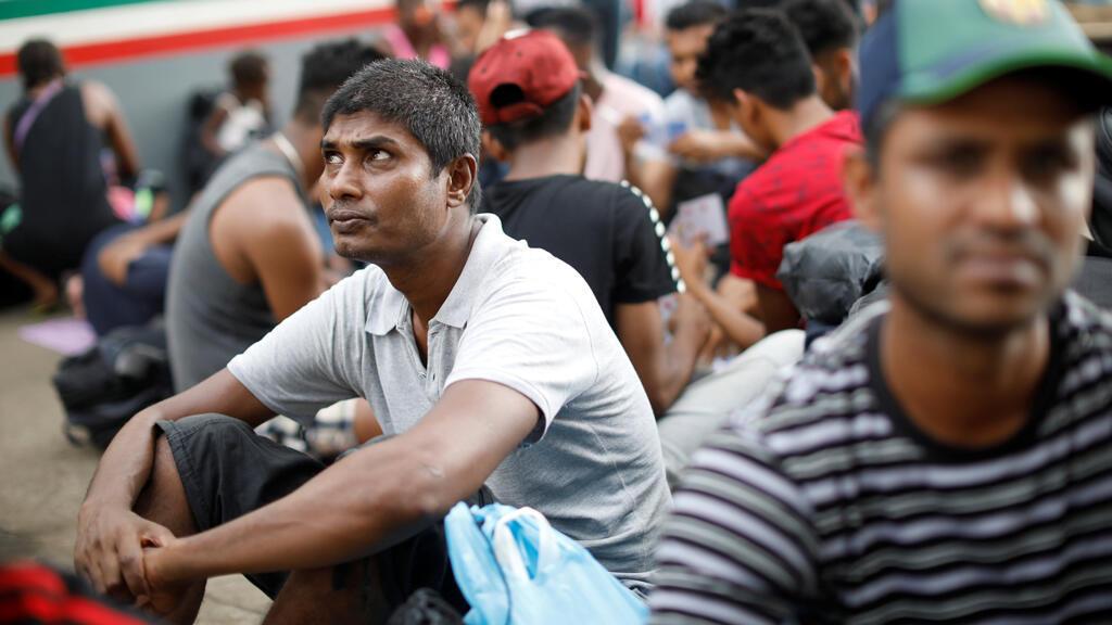Migrantes, que dicen ser de Bangladesh, se sientan afuera de las instalaciones migración de Siglo XXI en Tapachula, México, el 10 de mayo de 2019.