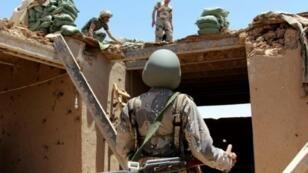 شرطي أفغاني يعاين موقعا أصيب بأضرار في غارة جوية في ولاية هلمند 10 حزيران/يونيو 2017