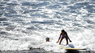 Surf's up at El Zonte beach in El Salvador, where a girl stands on a surf board next to her volunteer instructor