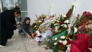Des touristes allument des bougies, vendredi 27 mars, devant le musée du Bardo à Tunis.