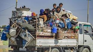 Una familia llega cerca de la ciudad de Hasaké, al norte de siria, después de huir de bombardeos del Ejército turco el 10 de octubre de 2019.