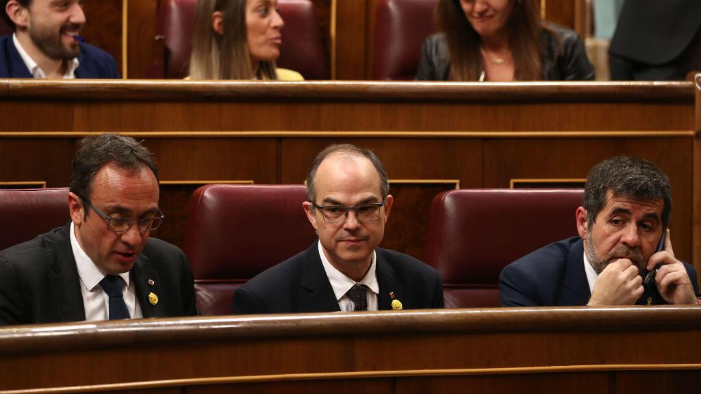En esta foto tomada el 21 de mayo de 2019, los recién elegidos y encarcelados miembros del parlamento catalanes JxCAT, diputado Jordi Sanchez (derecha), Jordi Turull (centro) y Josep Rull (izquierda) asisten a la primera sesión plenaria de la Cámara Baja.