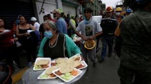 Una mujer se encarga de la distribución de alimentos a las víctimas del terremoto.
