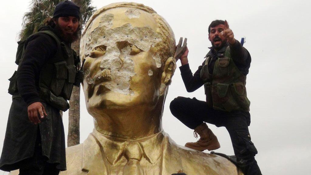 Des hommes du Front al-Nosra détruisent une statue de Hafez al-Assad, le père de Bachar al-Assad, le 28 mars 2015 à Idleb.