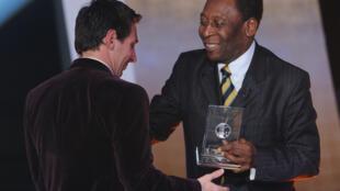 El delantero argentino del Barcelona Lionel Messi (I) recibe de la leyenda del fútbol brasileño Pelé el premio FIFA/FIFPro World XI, el 9 de enero de 2012 en Zúrich