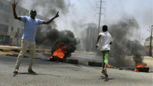 Des manifestants brûlent des pneus en guise de barricades près du QG de l'armée, et demandent au Conseil militaire soudanais de redonner le pouvoir aux civils, à Khartoum, le 3 juin 2019.