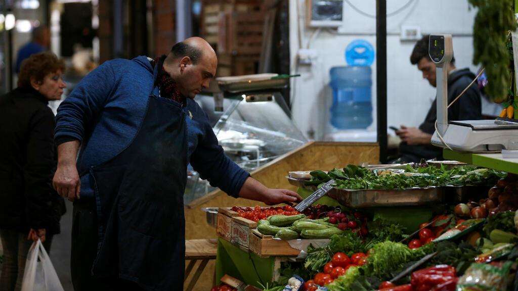 un comerciante organiza verduras en su puesto, en un mercado local, en Buenos Aires, Argentina , el 23 de agosto de 2019.