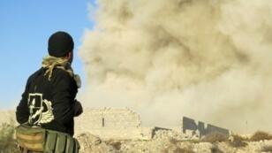 Un membre des forces progouvernementales irakiennes regarde la fumée s'élever de Ramadi, à 110 km à l'ouest de Bagdad, le 27 décembre 2015.