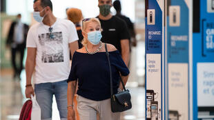 People wearing protective face masks due to the COVID-19 pandemic, walk in 'Les Terrasses du Port' commercial centre in Marseille on July 20, 2020, as masks become mandatory in all indoor public spaces.