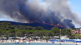 À Bormes-les-Mimosas, des plaisanciers quittent la plage mercredi 26 juillet à cause du feu de forêt tout proche.