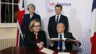 Theresa May et Emmanuel Macron assistant à la signature du nouveau traité par les ministres britannique et français de l'Intérieur.