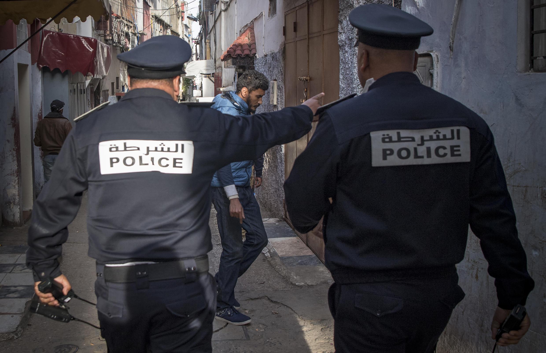 عناصر من قوات الأمن المغربية في أحد شوارع الرباط يدعون الناس الى التزام الحجر الصحي في منازلهم في 27 مارس/آذار 2020.