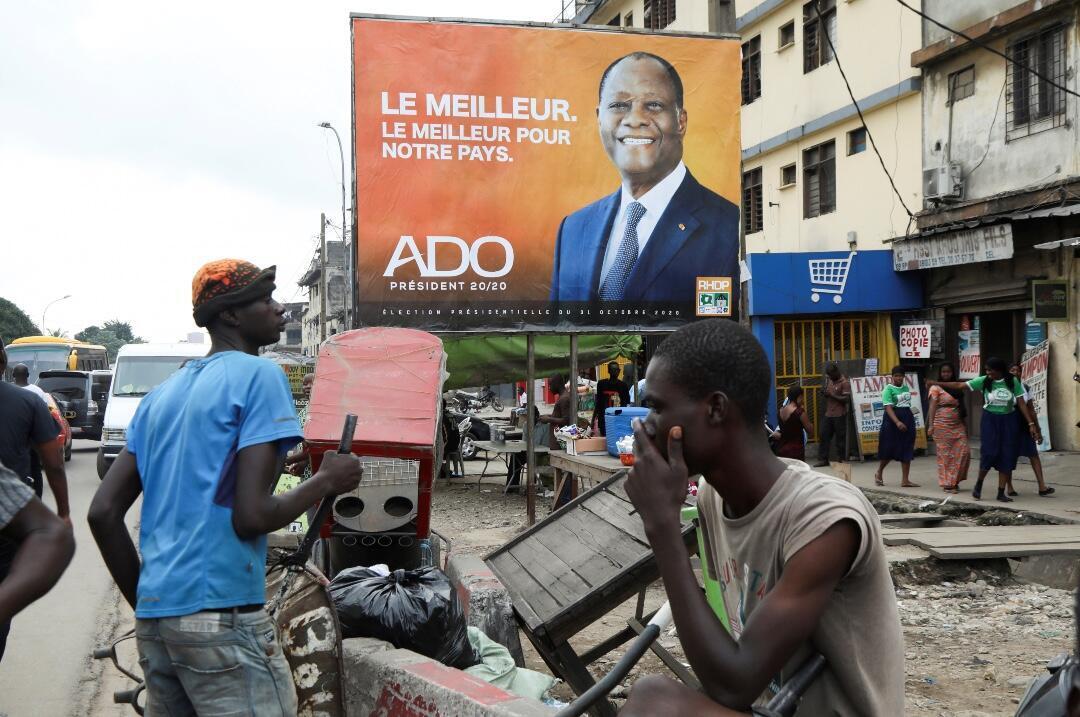 Ciudadanos ante un cartel de campaña del candidato presidencial Alassane Ouattara de la coalición gobernante RHDP en el distrito de Adjame, Abidjan, Costa de Marfil, el 15 de octubre de 2020.
