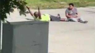Capture vidéo de l'homme noir allongé aux côtés de son patient autitse, à terre, les bras lévés, à Miami, lundi 18 juillet.