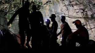 Los trabajadores de rescate toman un descanso mientras sacan las máquinas que ayudaron a la liberación de 12 jugadores de fútbol y su entrenador en el complejo de cuevas Tham Luang en la provincia norteña de Chiang Rai, Tailandia, el 10 de julio de 2018.