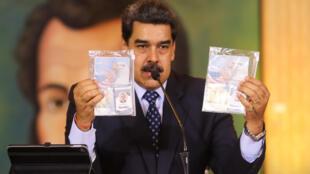 صورة وزعتها الرئاسة الفنزويلا للرئيس نيكولاس مادورو في كراكاس بتاريخ 6 أيار/مايو 2020 وهو يعرض جوازي سفر المواطنين الأميركيين اللذين أوقفتهما السلطات