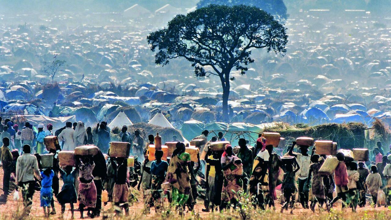 Génocide au Rwanda. Foule de réfugiés rwandais transportant leurs biens vers le camp de Benaco (Tanzanie), mai 1994.