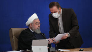 A handout picture provided by the Iranian presidency shows President Hassan Rouhani (L) talking with presidential chief of staff Mahmoud Vaezi during a cabinet session