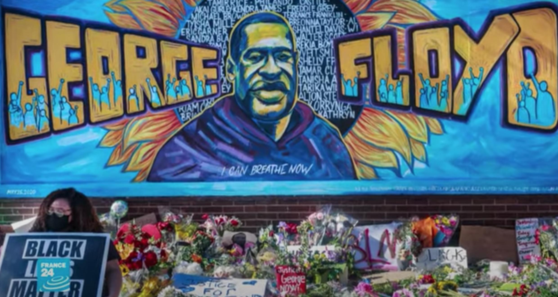 """متظاهرة ترفع لافتة كتب عليها """"حياة السود مهمة"""" وخلفها جدارية غرافيتي ضخمة لبورتريه جورج فلويد الأمريكي من أصول إفريقية الذي قتله شرطي أبيض في مدينة مينيابوليس. 25 مايو/أيار 2020."""
