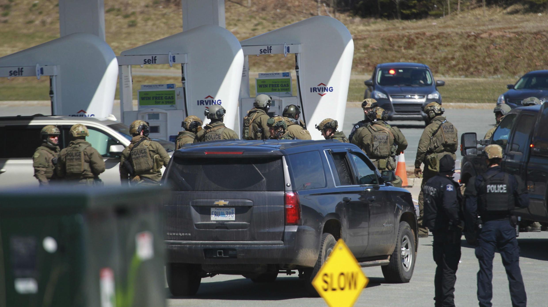 Oficiales de la Real Policía Montada de Canadá aparecen preparándose para trasladar al sospechoso, desde una estación de servicio en Enfield, Nueva Escocia, Canadá, el 19 de abril de 2020.
