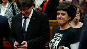 La integrante izquierdista del partido CUP Anna Gabriel (R) pasa junto al presidente catalán Carles Puigdemont durante un debate en el parlamento regional catalán en Barcelona, España, el 10 de octubre de 2017.