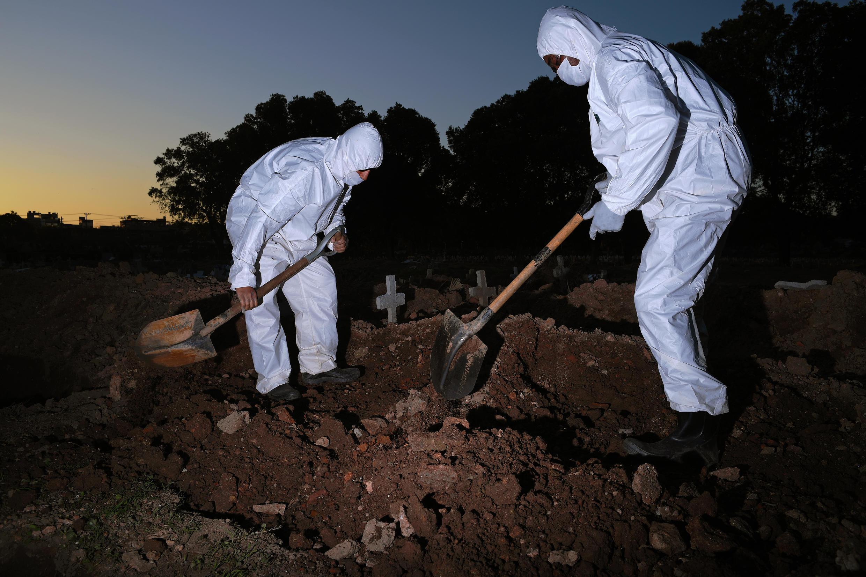 Los trabajadores usan ropa protectora para enterrar a una víctima de COVID-19 en el cementerio de Sao Francisco Xavier en Río de Janeiro, Brasil, el 29 de mayo de 2020.