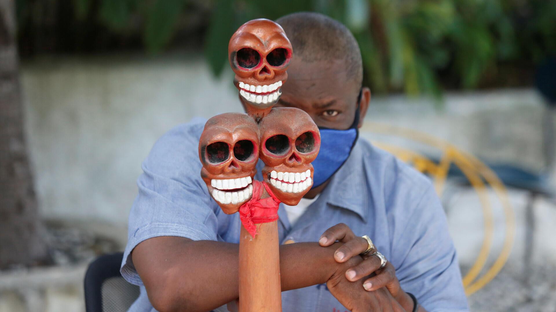 Un sacerdote vudú con una máscara facial para protegerse de la propagación de la enfermedad por coronavirus (COVID-19) participa en una ceremonia en Puerto Príncipe, Haití, 1 de mayo de 2020. Fotografía tomada el 1 de mayo de 2020.