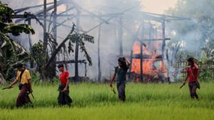 Des hommes armés de couteaux et de lance-pierres passent devant une maison en flammes, le 7 septembre 2017 dans l'État birman de Rakhine, où se trouvent de nombreux Rohingya.