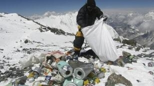 A sherpa collecting garbage left by climbers at an altitude of 8,000 metres on the Nepal side of Mount Everest. China is now closing to non-climbers the base camp on the Tibet side of the mountain because of environmental concerns