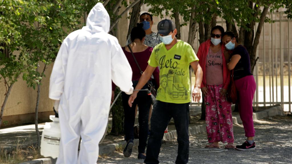 Los asistentes a un funeral de una mujer fallecida por Covid-19 son desinfectados antes de la ceremonia.