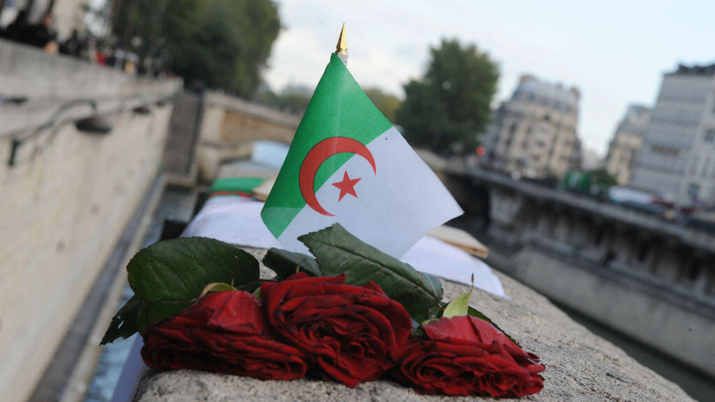 العلم الجزائري وورود حمراء عند جسر سان ميشال في باريس في إطار إحياء ذكرى مظاهرة 17 أكتوبر 1961 عام 2009