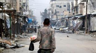 جندي من الجيش السوري يحمل الطعام ويسير في معرة النعمان، سوريا 30 يناير/كانون الثاني 2020.