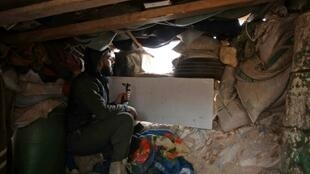 A fighter from the Syrian rebel National Liberation Front mans a position in Aleppo province on November 26, 2018