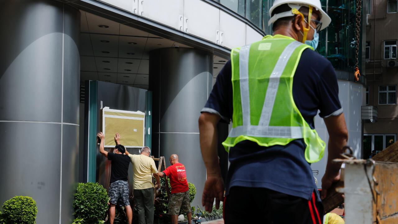 Trabajadores instalan un cartel en la fachada del Metropark Hotel Causeway Bay en Hong Kong en donde se dice que funcionará temporalmente la agencian de seguridad china. 7 de julio de 2020.