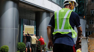Workers put up a board outside Metropark Hotel Causeway Bay, Hong Kong, believed to be used as the temporary national security agency in the city in Hong Kong, on July 7, 2020.
